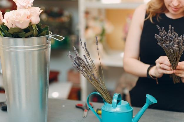 Kobieta kwiaciarnia zrobić bukiet w butiku kwiatowym.
