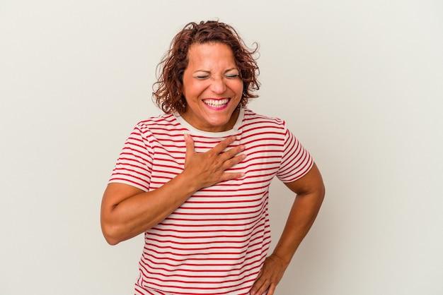 Kobieta łacińska w średnim wieku na białym tle śmiejąc się trzymając ręce na sercu, pojęcie szczęścia.