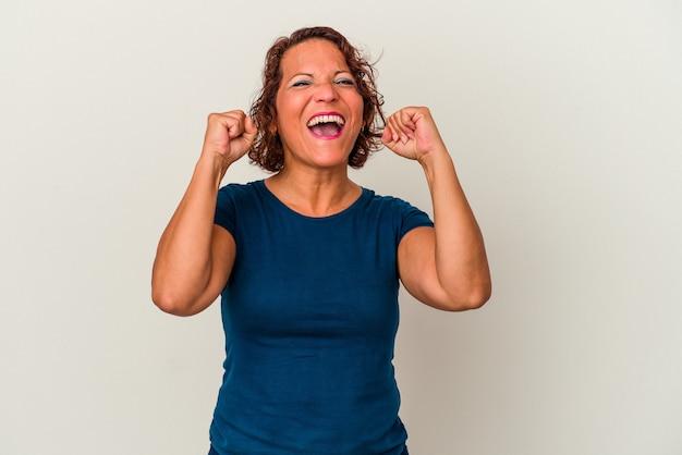 Kobieta łacińska w średnim wieku na białym tle świętuje zwycięstwo, pasję i entuzjazm, szczęśliwy wyraz.