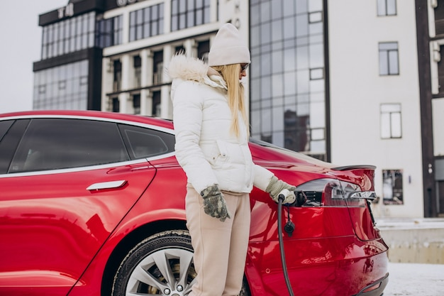 Kobieta ładująca czerwony samochód elektryczny, zimą