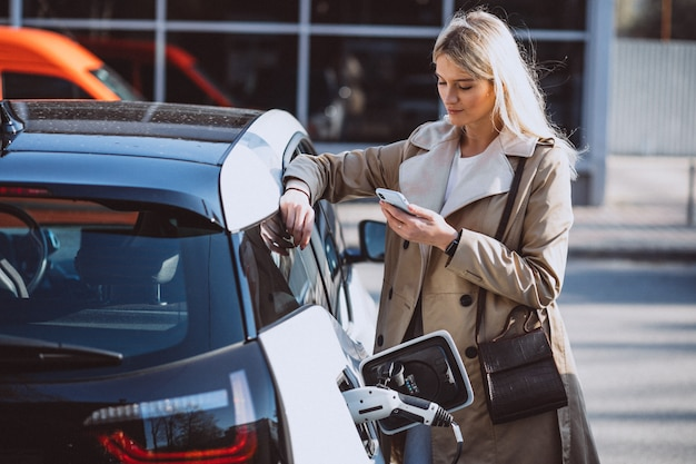Kobieta ładująca samochód elektryczny na stacji benzynowej