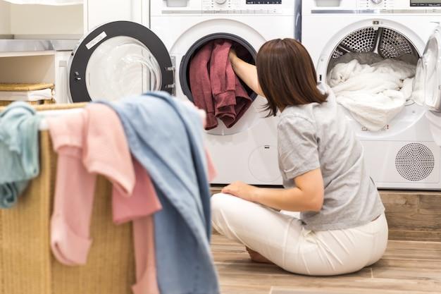 Kobieta ładuje brudne ubrania w pralce do prania w nowoczesnym pomieszczeniu gospodarczym
