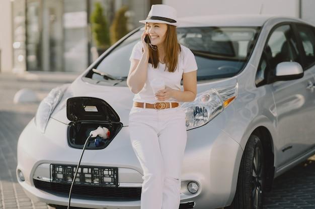Kobieta ładuje electro samochód przy elektryczną benzynową stacją