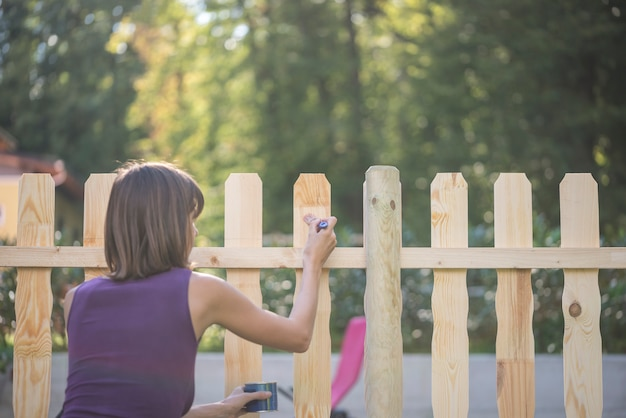 Kobieta lakieruje drewnianego palika ogrodzenie