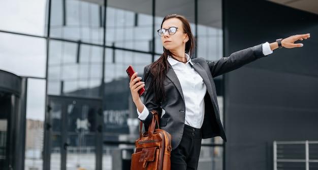 Kobieta łapie taksówkę. kobieta czeka na samochód i pojedzie na spotkanie biznesowe. pomysł na biznes. dziewczyna w okularach w mieście w pobliżu pracy.