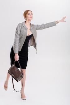 Kobieta łapie taksówkę. młoda piękna biznesowa blondynka w czarnej sukience, kurtka macha, aby zatrzymać taksówkę na szarym tle