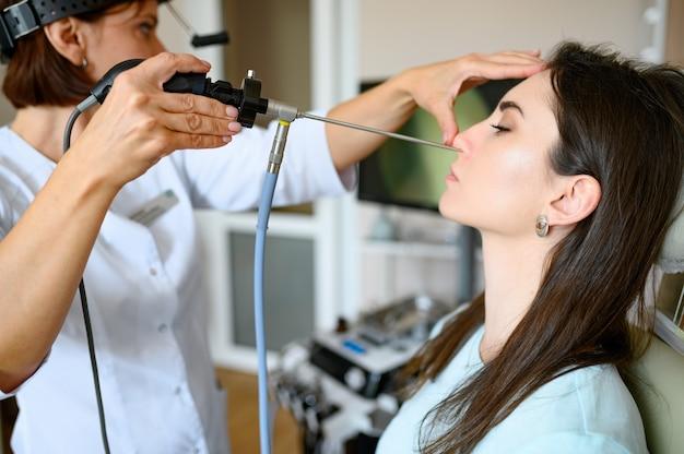 Kobieta laryngolog i pacjent w fotelu, egzamin. badanie nosa w poradni, profesjonalna diagnostyka, lekarz. lekarz specjalista i kobieta w szpitalu
