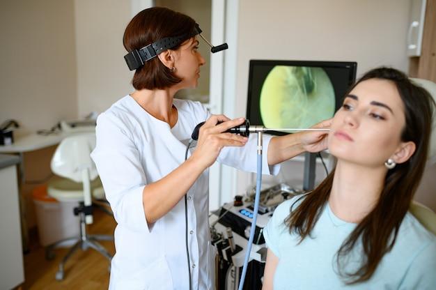 Kobieta laryngolog i pacjent w fotelu, otoskop. badanie ucha w poradni, profesjonalna diagnostyka, lekarz. lekarz specjalista i kobieta w szpitalu
