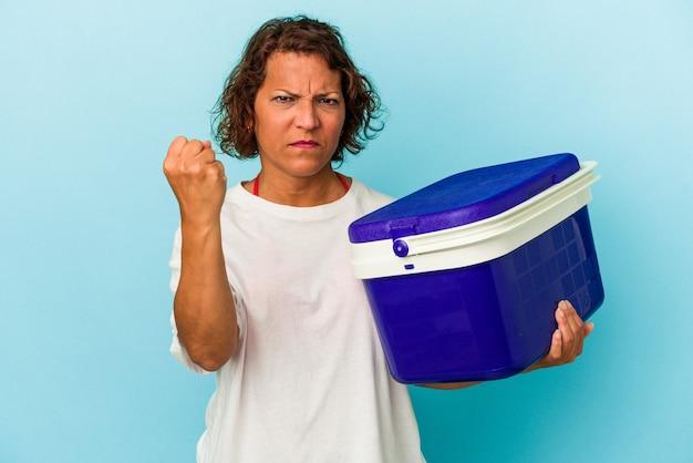 Kobieta latynoska w średnim wieku na białym tle na niebieskim tle pokazując pięść do kamery, agresywny wyraz twarzy.