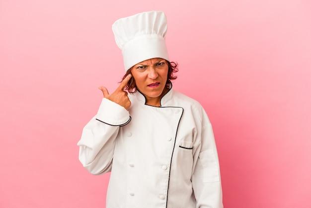 Kobieta latynoska w średnim wieku na białym tle na różowym tle pokazując gest rozczarowania palcem wskazującym.