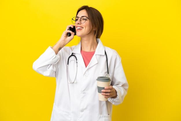 Kobieta lekarka na żółtym tle trzymająca kawę na wynos i telefon komórkowy