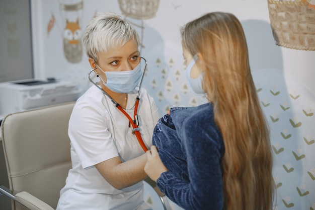 Kobieta lekarz bada dziecko. dziewczyna w gabinecie pediatry.