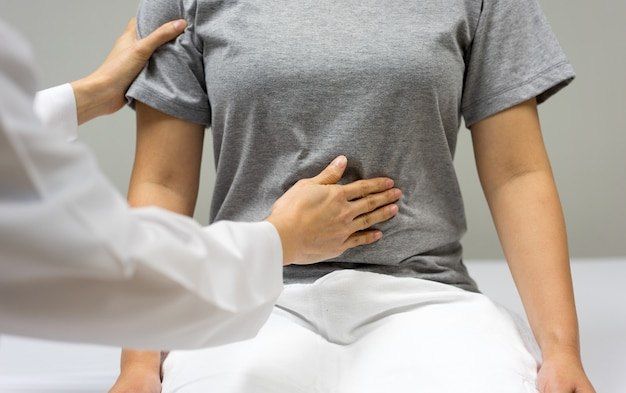 Kobieta lekarz bada przez omacywanie brzucha pacjentki siedzącej w łóżku w klinice.
