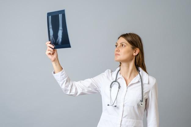 Kobieta lekarz bada zdjęcie rentgenowskie nóg noworodka. na białym tle na szarej ścianie