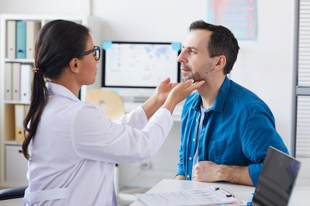 Kobieta lekarz badający gardło pacjenta, siedząc w szpitalu podczas wizyty