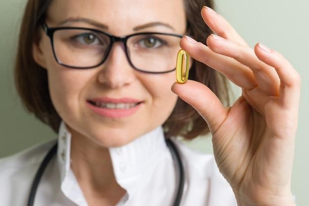 Kobieta lekarz bierze kapsułkę witaminy