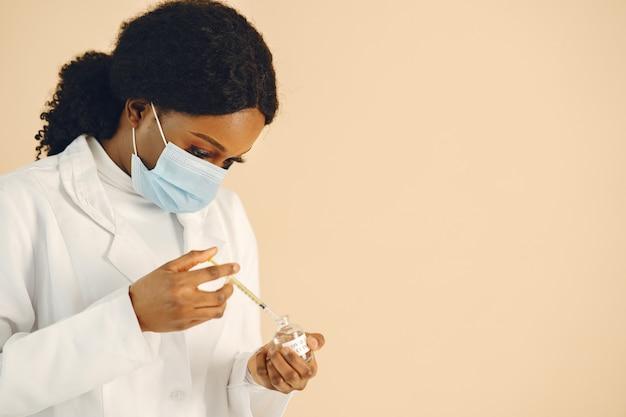Kobieta lekarz biorąc szczepionkę ze strzykawki z ampułki, zapobieganie epidemii.
