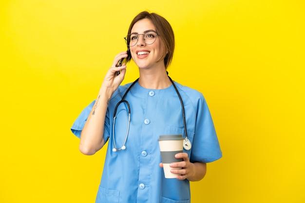 Kobieta lekarz chirurg odizolowana na żółtym tle trzymająca kawę na wynos i telefon komórkowy