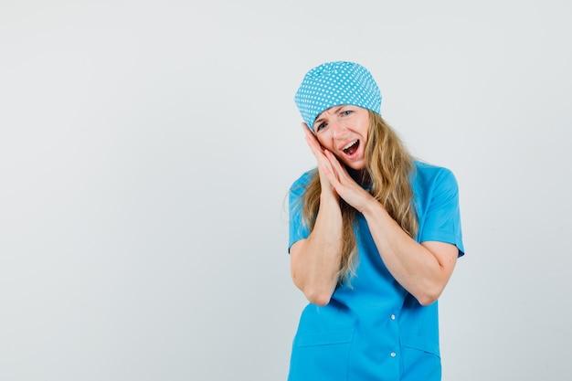 Kobieta lekarz cierpi na ból zęba w niebieskim mundurze