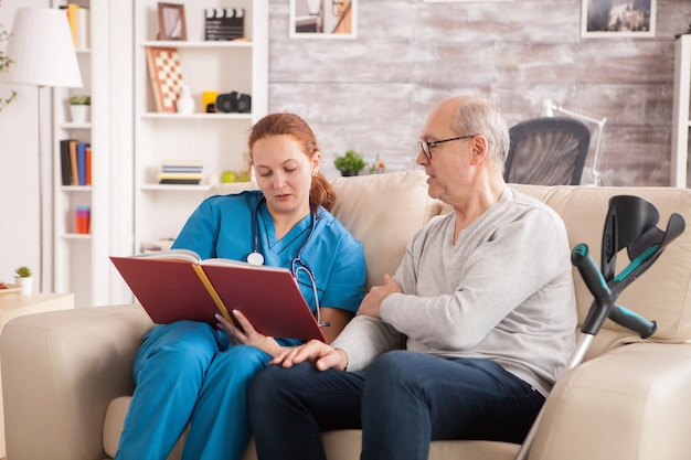Kobieta lekarz czyta książkę do starca w domu opieki.