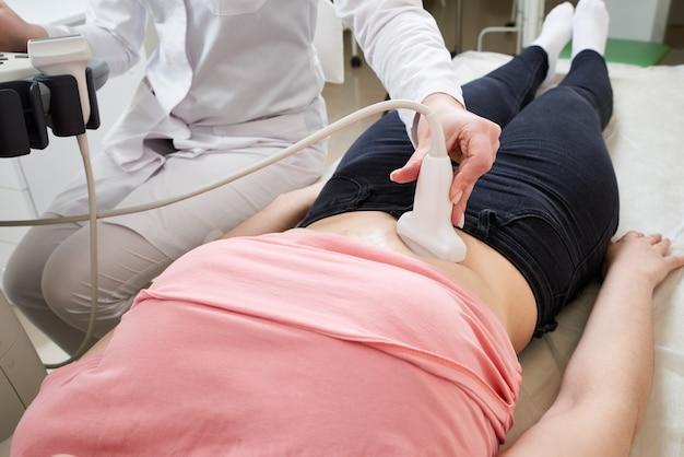Kobieta lekarz ginekolog obsługujący ultrasonograf