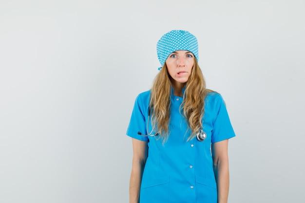 Kobieta lekarz gryzie wargę w niebieskim mundurze i wygląda zapominalski