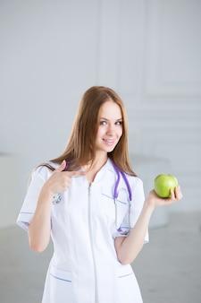 Kobieta lekarz jest dietetykiem z zielonym jabłkiem