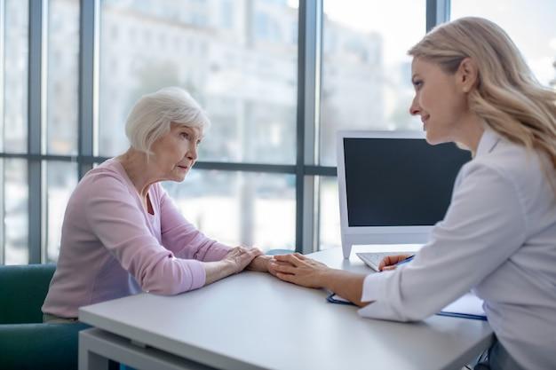 Kobieta lekarz kładzie rękę na rękę pacjentów, pokazując zaniepokojenie