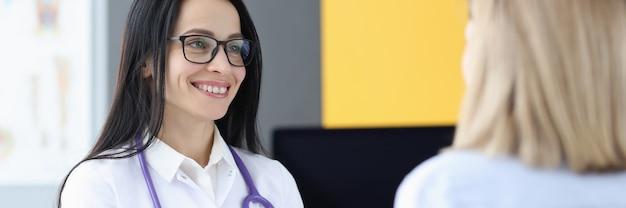 Kobieta lekarz komunikuje się z pacjentem w klinice biorąc koncepcję anamnezy