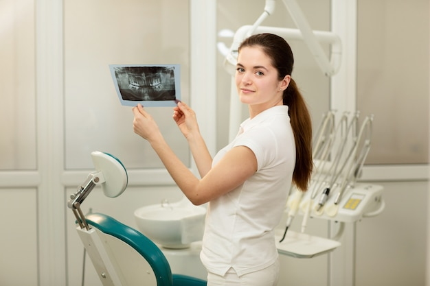 Kobieta lekarz lub dentysta patrzeje promieniowanie rentgenowskie. pojęcie opieki zdrowotnej, medycznej i radiologii