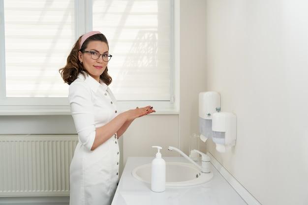 Kobieta lekarz lub farmaceuta mycie i dezynfekcja rąk środkiem dezynfekującym i mydłem