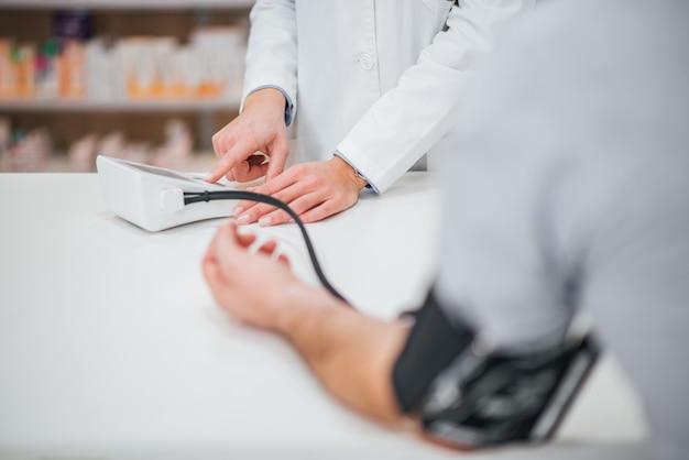 Kobieta lekarz lub farmaceuta pomiaru ciśnienia krwi pacjenta płci męskiej.