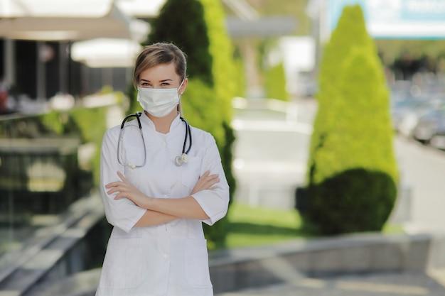 Kobieta lekarz lub pielęgniarka ubrana w maskę ochronną ze stetoskopem na szyi