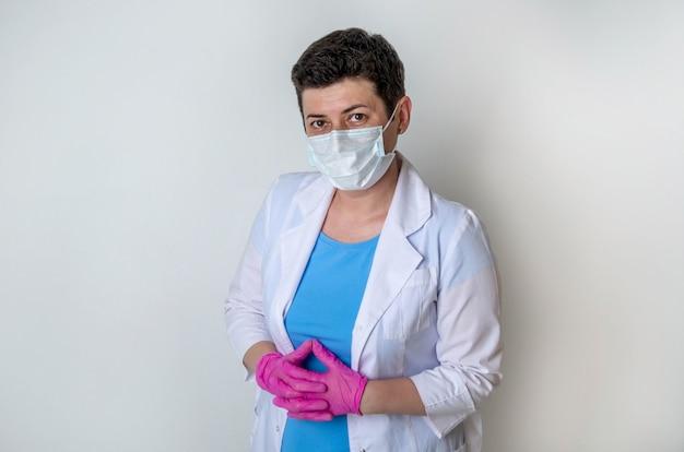 Kobieta, lekarz lub pielęgniarka, ubrana w suknię medyczną z jednorazową maską na twarz, stoi w pobliżu białej ściany