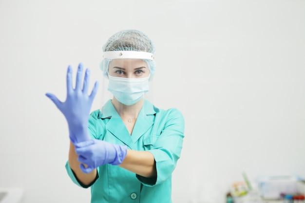 Kobieta lekarz lub pielęgniarka w mundurze, maska medyczna, osłona twarzy nakłada rękawiczki. koronawirus (covid-19. dziewczyna, kobieto.