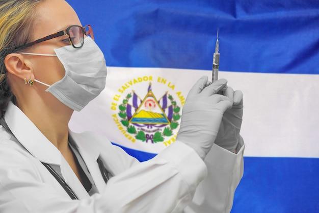 Kobieta lekarz lub pielęgniarka w rękawiczkach trzymając strzykawkę do szczepień na tle flagi salwadoru