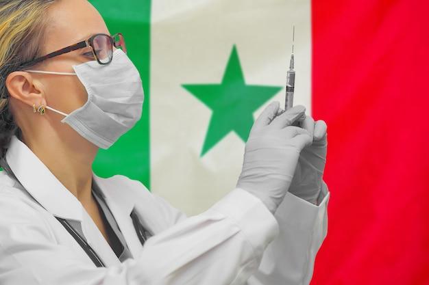 Kobieta lekarz lub pielęgniarka w rękawiczkach trzymając strzykawkę do szczepień na tle flagi senegalu