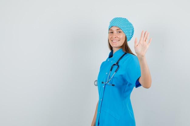 Kobieta lekarz macha ręką i uśmiecha się w niebieski jednolity widok z przodu.