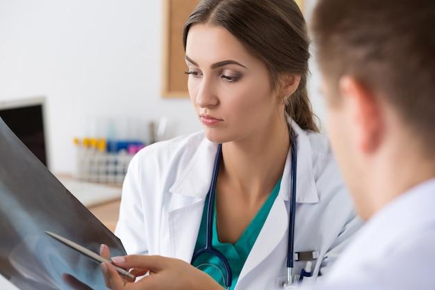 Kobieta lekarz medycyny pokazując coś swojemu koledze na zdjęciu rentgenowskim