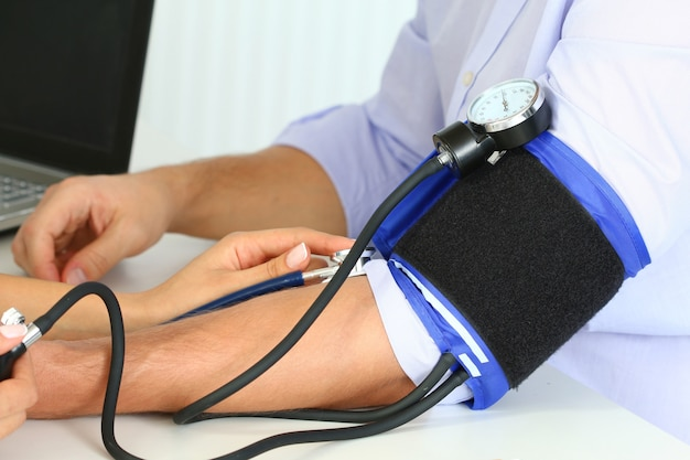 Kobieta lekarz medycyny pomiaru ciśnienia krwi do swojego pacjenta