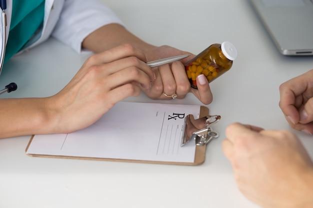Kobieta lekarz medycyny przepisywania tabletek pacjentowi