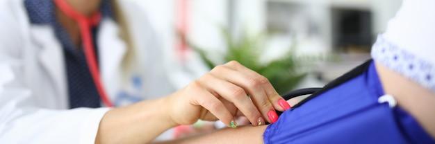 Kobieta lekarz mierzy ciśnienie zbliżenia pacjenta