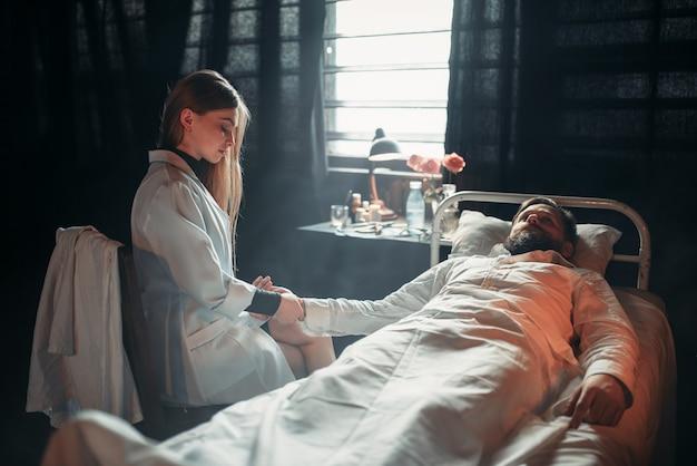Kobieta lekarz mierzy puls chorego mężczyzny