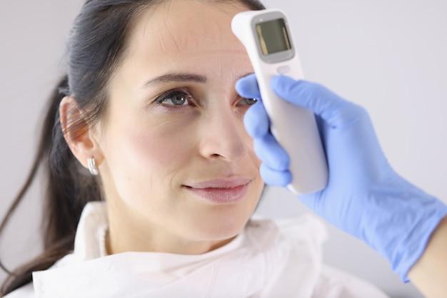 Kobieta lekarz mierzy temperaturę ciała po zmianie