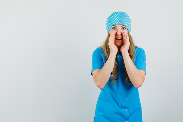 Kobieta lekarz mówi sekret z rękami w pobliżu ust w niebieskim mundurze i wygląda zaciekawiony