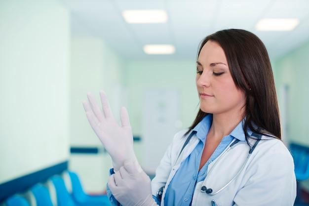 Kobieta lekarz nosi rękawiczki chirurgiczne