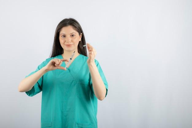 Kobieta lekarz nosi zielony mundur trzymając strzykawkę na białym.