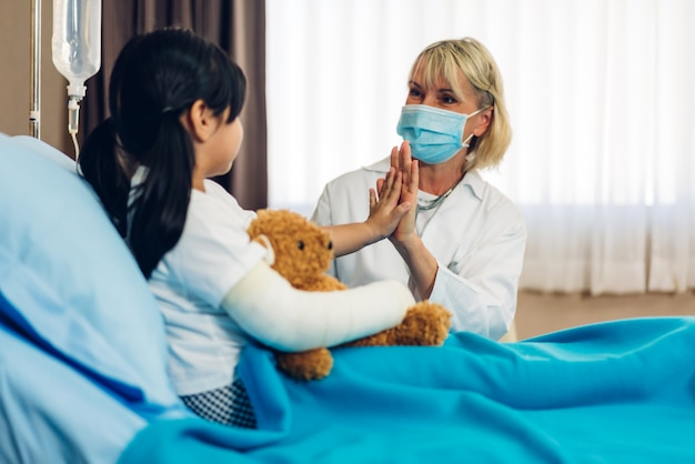 Kobieta lekarz noszenie maski rozmawia z małym pacjentem