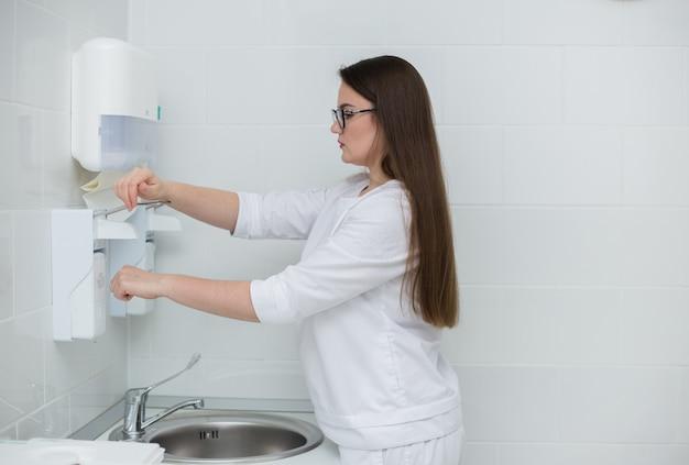 Kobieta lekarz o brązowych włosach w białym fartuchu lekarskim wstaje i myje ręce