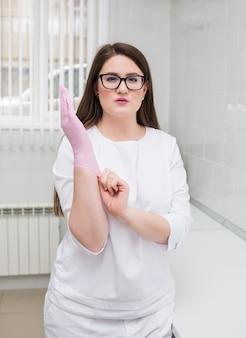 Kobieta lekarz o brązowych włosach w okularach i białym garniturze zakłada w biurze jednorazowe różowe rękawiczki